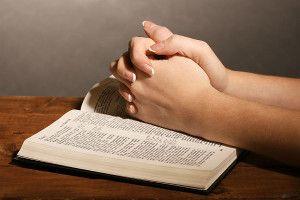 Руки, складені в молитві на біблії